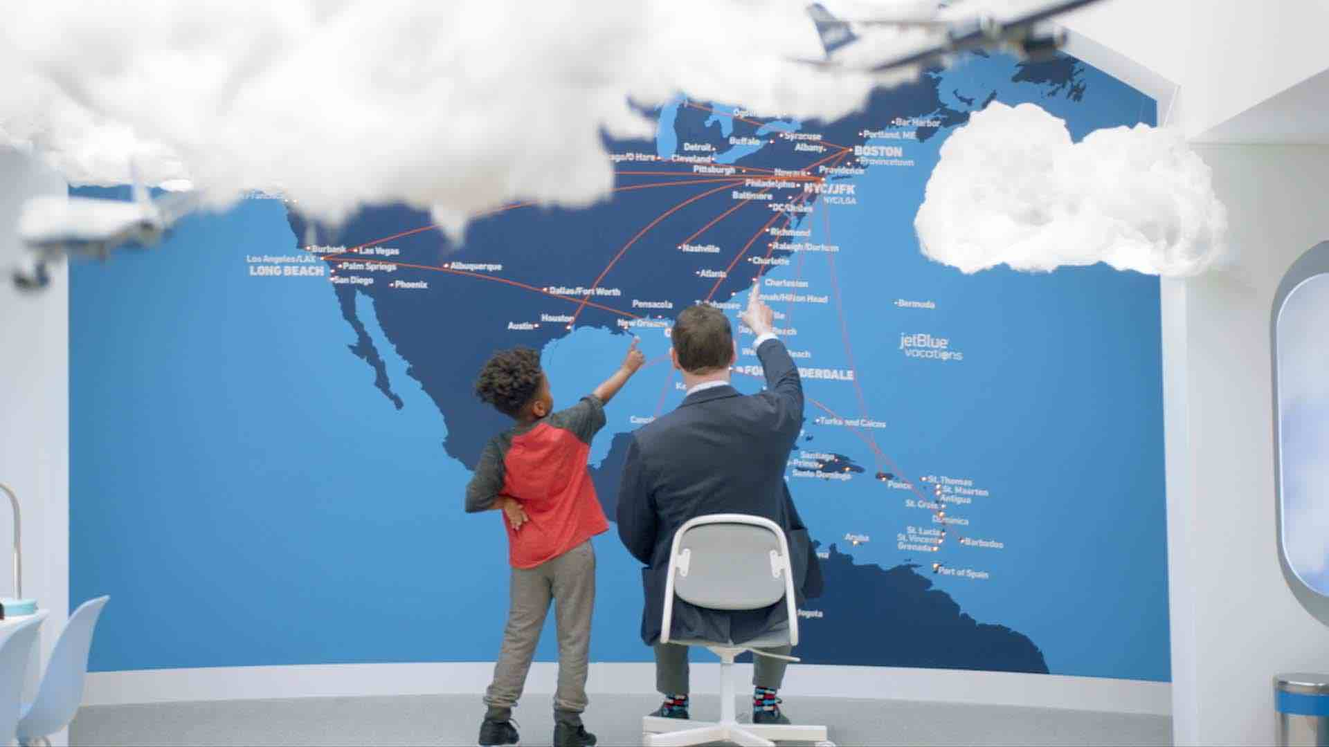 Thumbnail for a commercial for JetBlue called 'Little Tickets' showing a man and a young boy pointing at a map of flight paths.